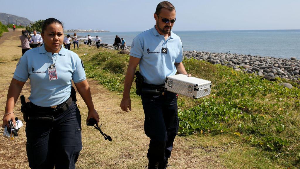 Des gendarmes français rapportant des débris d'avion découverts à La Réunion, le 2 août 2015.
