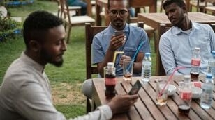 Mohamed Omar (L) sits with his friends at a cafe in an upscale district of Sudan's capital on June 17, 2019