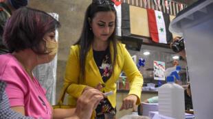 ناخبة في أحد مراكز الاقتراع في الانتخابات التشريعية في سوريا في مدينة حلب في 19 تموز/يوليو 2020