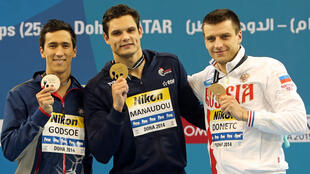Florent Manaudou, vainqueur du 50 mètres dos, pose avec sa médaille d'or aux côtés d'Eugène Godsoe (États-Unis, à gauche) et Stanislav Donets (Russie à droite) lors des Mondiaux-2014 en petit bassin à Doha au Qatar.
