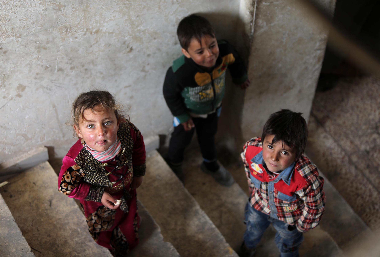 Niños miran en la escalera de una casa en las cercanías de la ciudad de Tal Abyad, en el norte de Siria, donde muchas familias del sur de la provincia de Alepo han huido tras el bombardeo de las fuerzas del gobierno sirio.