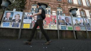Un jeune homme passe devant les affiches officielles de campagne des 11 candidats à la présidentielle, le 10 avril à Strasbourg.