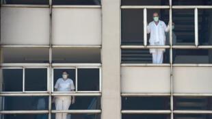 Dos sanitarios se asoman por la ventana en el Hospital Universitario de La Coruña el 26 de marzo de 2020