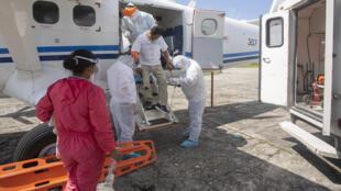 Un trabajador médico (C) que muestra síntomas del nuevo coronavirus COVID-19 desciende de una pequeña aeronave en Iquitos, en la selva amazónica del norte del Perú, al llegar de la comunidad de San Isidro, el 11 de julio de 2020.