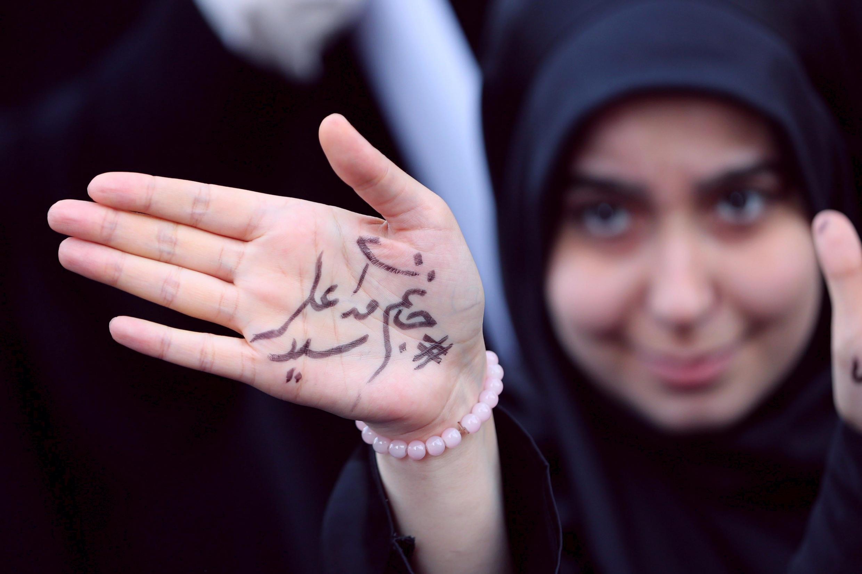 """Una joven muestra un mensaje en su mano que dice """"estamos preparados para sacrificarnos por el líder supremo, el ayatolá Ali Jameini"""", en una protesta contra las sanciones impuestas por Washington. Teherán, Irán, el 4 de noviembre de 2018."""