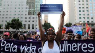 """Una mujer sostiene una señal de tránsito que dice """"Calle Mariele Franco"""" en tributo a la activista y consejera brasileña asesinada en 2018, en medio de una manifestación por el Día Internacional de la Mujer. Río de Janeiro, Brasil, el 8 de marzo de 2019."""
