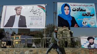 Un Afghan passe devant des panneaux électoraux à Kaboul le 28 septembre.