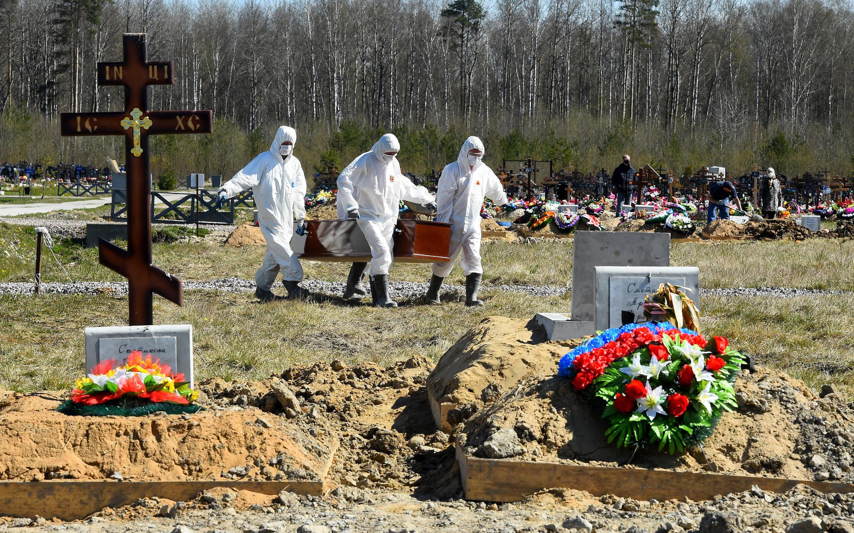 Los trabajadores del cementerio con equipos de protección entierran a una víctima de coronavirus en un cementerio en las afueras de San Petersburgo. Rusia ha reportado una tasa de mortalidad notablemente baja, pero los críticos han puesto en duda las cifras.
