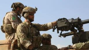 Combattants présentés par les Forces démocratiques syriennes (FDS), coalition menée par le PYD kurde, comme des soldats américains, le 25 mai au nord de Raqqa. Sur leur épaule l'insigne du PYD.