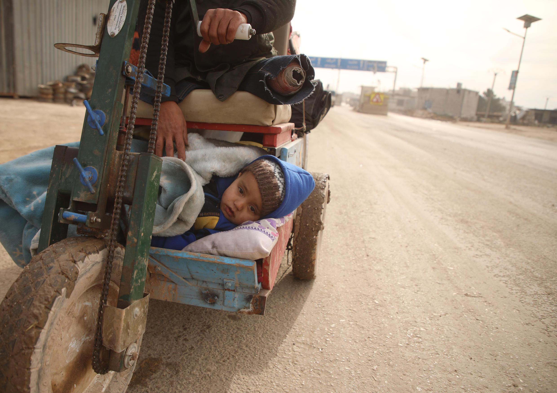 Un niño sirio yace bajo una manta en un triciclo improvisado mientras los civiles huyen de la ciudad de Atareb en el campo occidental controlado por los rebeldes de la provincia de Alepo de Siria durante el bombardeo de las fuerzas gubernamentales el 11 de febrero de 2020