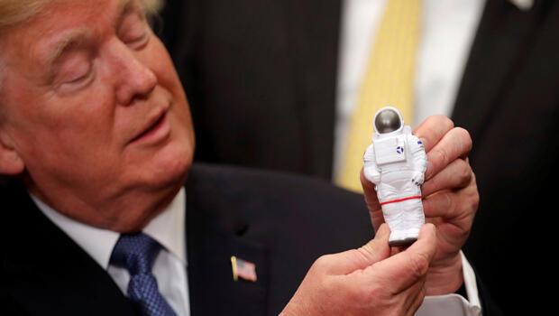El presidente de EE. UU., Donald Trump, sotiene un astronauta espacial de jueguete mientras participa en una ceremonia de firma de la Directiva de Política Espacial en la Casa Blanca en Washington D.C., EE. UU., el 11 de diciembre de 2017.