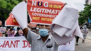 """متظاهر يرفع لافتة كتب عليها أن """"حكومة الوحدة الوطنية"""" هي الحكومة الشرعية في بورما"""