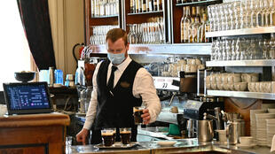 A waiter prepares coffee at Café Einstein in Berlin on May 15, 2020, as coronavirus lockdown measures were eased and cafés and restaurants were allowed to reopen.