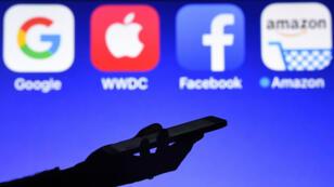 Esta fotografía tomada el 28 de septiembre de 2017, muestra un teléfono inteligente operado frente a los logotipos de GAFA (acrónimo de Google, Apple, Facebook y Amazon).