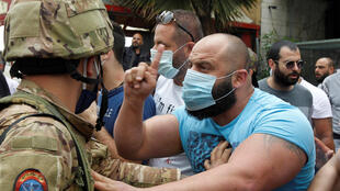 A Lebanese demonstrator gestures to a Lebanese soldier, during a protest against the collapsing Lebanese pound currency and the price hikes, in Zouk, north of Beirut, Lebanon April 27, 2020.