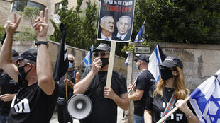 An Israeli protester holds a placard with a picture of Prime Minister Benjamin Netanyahu and his former rival Benny Gantz in Jerusalem