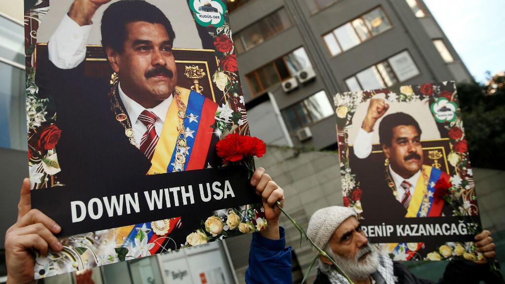 Manifestantes sostienen pancartas mientras se congregan en apoyo al gobierno del presidente venezolano Nicolás Maduro,  frente al Consulado de Venezuela en Estambul, Turquía, el 1 de febrero de 2019.