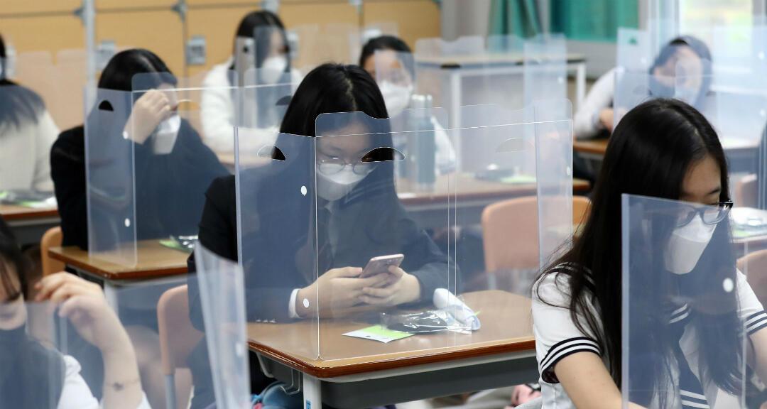 Estudiantes esperan que la clase comience con paneles de plástico colocados en sus escritorios en la Escuela Secundaria Jeonmin en Daejeon, Corea del Sur.