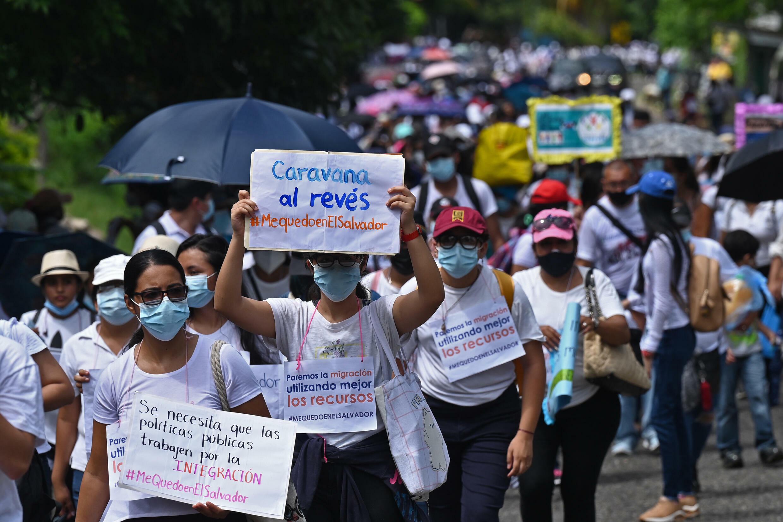 """Una mujer sostiene una pancarta que dice """"Caravana al revés"""" en una marcha de jóvenes bajo el lema """"Me quedo en El Salvador"""", en Las Chinamas, El Salvador, el 9 de octubre de 2021"""