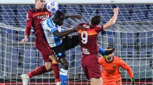Le défenseur de l'AS Rome, Gianluca Mancini, dégage le ballon devant son homologue de Naples, le Sénégalais Kalidou Koulibaly, et son coéquipier bosniaque, Edin Dzeko, lors de leur match de Série A, le 21 mars 2021 au stade Olympique à Rome