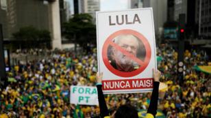 Seguidor de Jair Bolsonaro sostiene un cartel con la imagen del expresidente brasileño, Luiz Inácio Lula da Silva, en una manifestación en Sao Paulo. Brasil, 21 de octubre de 2018.