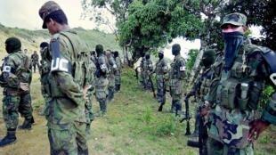 Integrantes de un grupo paramilitar a unos 480 kilómetros de Bogotá el 12 de junio de 2000. Miembros del frente de Farellones, de los grupos paramilitares de las autoproclamadas Fuerzas de Autodefensa Unidas de Colombia (AUC), realizan ejercicios cerca de Cali, a unos 480 km al sureste de Bogotá, el 12 de junio de 2000. A la extrema derecha Paramilitares, quienes harán incursiones en esta región, están acusados de secuestrar al menos a 111 personas entre enero y mayo de este año, según Jesús Bohorquez, coronel colombiano y jefe del grupo Antiextorsion and Secuestration of the Army (Gaula). Además, hoy se les adjudicó el asesinato de un campesino que, según ellos, colaboró con la guerrilla y fue encontrado muerto en la ciudad de Liberia.