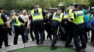"""La policía impide el paso a manifestantes de izquierda durante un acto de campaña del partido de ultra derecha, """"Alternativa para Suecia"""" celebrado en el parque Kings´s Garden. Estocolmo, Suecia. 7 de septiembre de 2018."""
