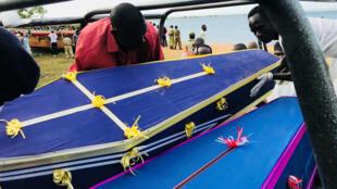 Voluntarios ayudan a llevar los ataúdes que contienen los cuerpos hallados tras el hundimiento del ferri en el lago Victoria. 22 de septiembre de 2018.