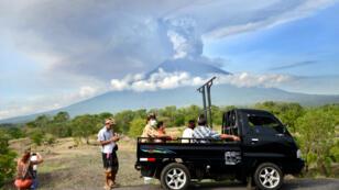 Des habitants de l'île de Bali, en Indonésie, regardent, lundi 27 novembre 2017, la fumée s'échapper du Mont Agung.