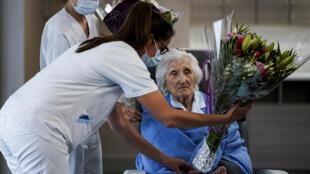 Una trabajadora de la salud obsequia un ramo de flores a la paciente belga de 100 años Julia Dewilde, luego de recibir el alta del centro hospitalario Bois de l'Abbaye en Seraing, cerca de Lieja, Bélgica, el 29 de abril de 2020