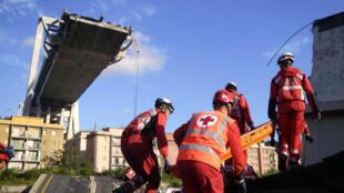Trabajadores de la Cruz Roja de Italia remueven escombros en las labores de búsqueda, rescate y limpieza, de la zona en donde cayeron los escombros del puente Morandi.