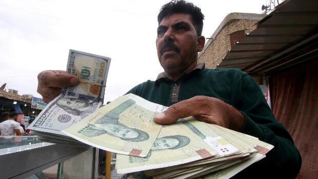 Un hombre sostiene en su manos riales iraníes y un billete de dólares estadounidenses en una tienda de cambio de divisas antes del inicio de las sanciones de Estados Unidos. Teherán, Irak, el 3 de noviembre de 2018.
