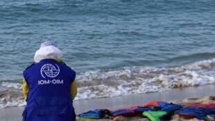 عامل إنقاذ من منظمة الهجرة الدولية يجلس أمام سترات نجاة مهاجرين غارقين متناثرة على الشاطئ بمدينة الخمس الليبية، 12 نوفمبر/تشرين الثاني 2020.