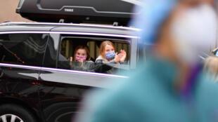 Des enfants masqués applaudissent en hommage aux soignants devant un hôpital new-yorkais, le 23 avril 2020