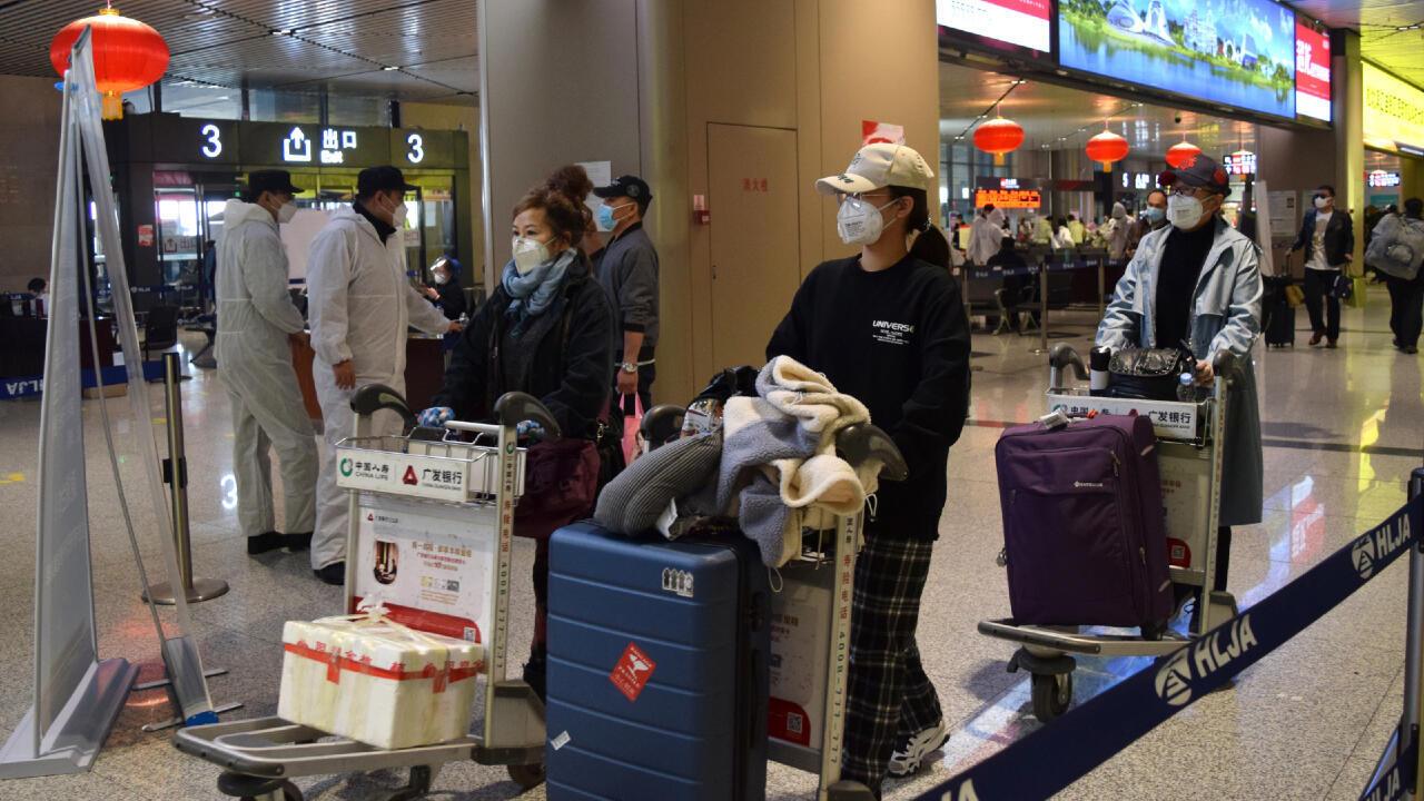 Los pasajeros con mascarillas empujan sus equipajes en un aeropuerto de Harbin, capital de la provincia de Heilongjiang que limita con Rusia. Harbin, China, el 11 de abril de 2020.