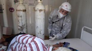 ممرضة تونسية ترتدي بدلة واقية ترعى مصابا بفيروس كورونا في وحدة رعاية مركزة بمستشفى في ولاية باجة شمال غرب البلاد بتاريخ 22 حزيران/يونيو 2021