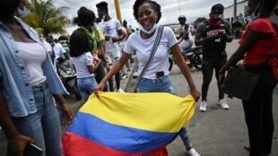 Un manifestante sostiene una bandera nacional de Colombia durante una protesta contra los grupos armados que han dejado este año 31 muertos en más de 30 enfrentamientos que luchan por el territorio en Buenaventura, Colombia, el 5 de febrero de 2021.