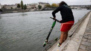 Un empleado del servicio de bicicletas compartidas Lime recoge una scooter eléctrica abandonada en el río Sena en París, Francia, el 25 de octubre de 2019.