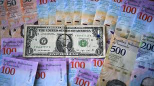 Des billets de la république bolivarienne et un billet d'un dollar américain, à Caracas, le 28 janvier 2019.