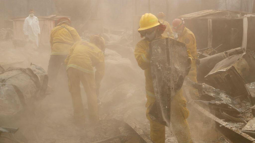 Los bomberos de Cal Fire y los voluntarios de búsqueda y rescate se internan en una casa destruida por el Camp Fire en la ciudad de Paradise, el 14 de noviembre de 2018.