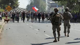 Soldados caminan hacia los manifestantes durante una protesta contra el modelo económico estatal de Chile en Santiago el 20 de octubre de 2019.