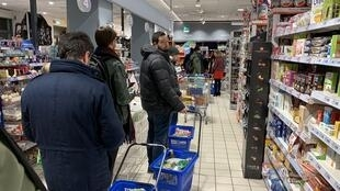 Customers queue to pay for food and essential products in a supermarket in Milan late on March 7, 2020, after Italy prepared to quarantine more than 10 million people around Milan and the tourist mecca Venice to halt the spread of the new coronavirus.