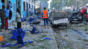 People stand among damages at the scene of a blast after two car bombs exploded in Mogadishu on October 28, 2017.