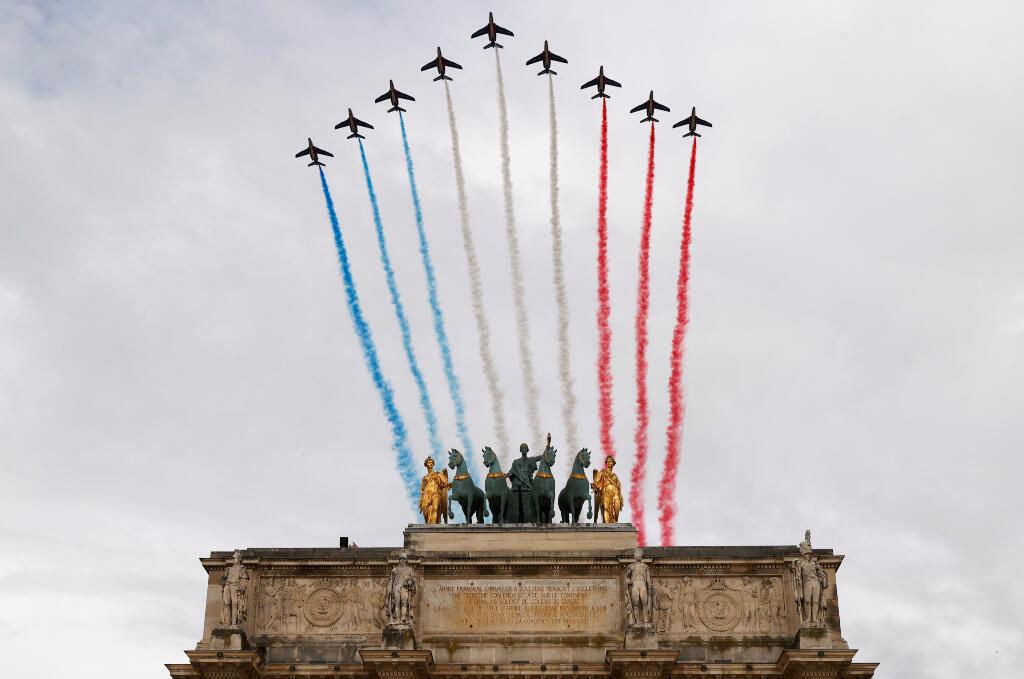 Los aviones Alpha de la Patrouille de France de la Fuerza Aérea Francesa pasan volando por el Arc de Triomphe du Carrousel, junto al museo del Louvre, durante las celebraciones del Día de la Bastilla en París, Francia, el 14 de julio de 2020.