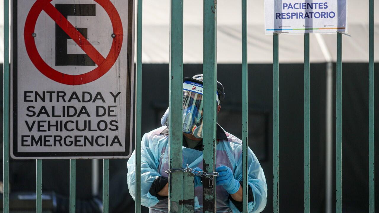 Un miembro del personal médico del Hospital San José de la ciudad de Santiago se dispone a abrir la puerta de entrada a la clínica. En Santiago, Chile, el 15 de mayo de 2020.