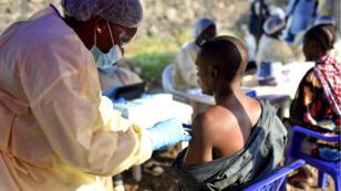 Un agent de santé congolais administre un vaccin contre le virus Ebola à un homme au Centre de santé Himbi à Goma (RDC), le 17 juillet 2019.