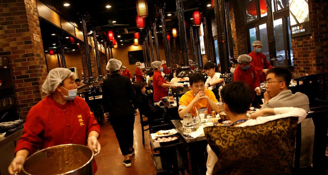 Trabajadoras de un restaurante usan gorros de plástico y mascarillas mientras atienden a los clientes en un restaurante tradicional en Beijing, China, el 5 de mayo de 2020.