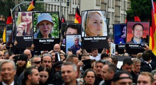 متظاهرون يرفعون صور ضحايا لمهاجرين خلال تجمع في  كيمنتس في الأول من أيلول/سبتمبر 2018