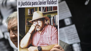 A demonstrator holds a picture of slain Mexican journalist Javier Valdez during a protest in Mexico City on May 16, 2017