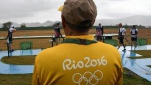 متطوع يشاهد المتسابقين يتدربون على مسابقة الحفرة المزدوجة للرماية في ريو دي جانيرو